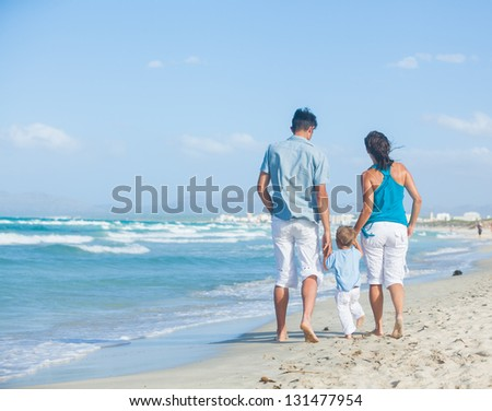 Back view of happy young family - mother, father and son having fun on the beach - stock photo