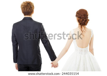 Back view of holding hands bride and groom isolated on white - stock photo