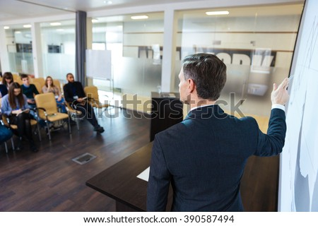 Back view of intelligent speaker on business conference in meeting hall - stock photo