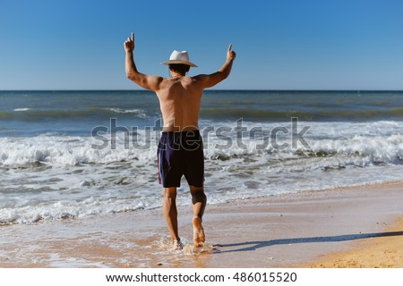 Back view of joyful man on the beach sunny blue sky outdoors background