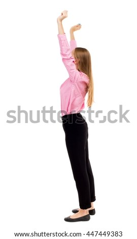 Back view of  joyful woman celebrating victory hands up. Rear view people collection. backside view person. Isolated over white background. girl in pink shirt standing sideways holding up both hands