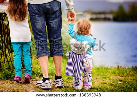 Back view of little baby girl and his family near lake - stock photo