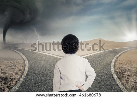 Back view of little businessman standing on the road while looking at two roads with sunlight and storm
