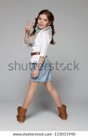Back view of little fashion smiling girl looking at camera over shoulder and showing victory sign - stock photo
