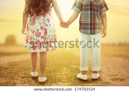 Back view of little girl and boy holding hands at sunset. Love concept - stock photo