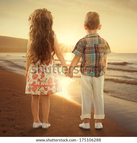 Back view of little girl and boy holding hands at sunset. Love, friendship concept - stock photo