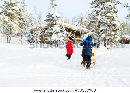 Back view of little girl and cute boy outdoors on beautiful winter day having fun playing in snow