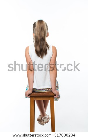 back view of little girl sitting on high chair - stock photo