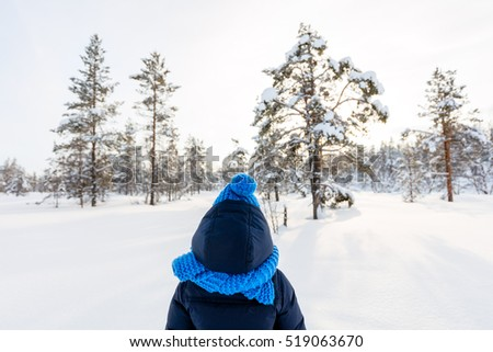 Back view of little girl wearing warm clothes outdoors on beautiful winter snowy day