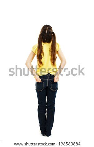 Back view of little girl with both hands in her pockets looking up at wall. Rear view. Isolated on white background  - stock photo