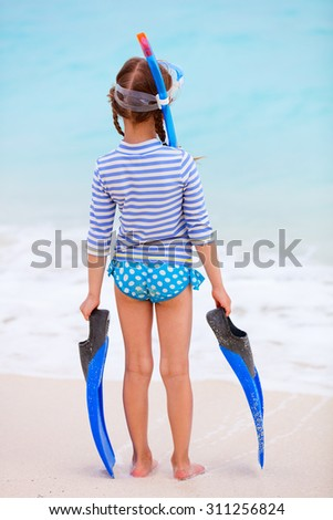 Back view of little girl with snorkeling equipment at beach during summer vacation - stock photo