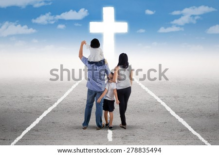 Back view of little happy family standing on the road and follow a cross - stock photo