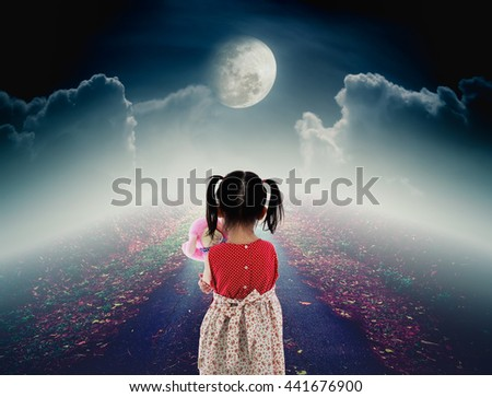 Back view of lonely child with doll sad gesture on pathway with a nightly sky and a large moon for halloween background. The moon were NOT furnished by NASA. - stock photo