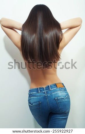 back view of long hair brunette wearing blue jeans, studio white