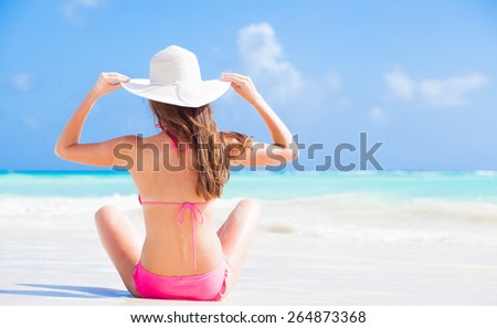 back view of long haired woman in bikini and wearing a hat on tropical beach - stock photo