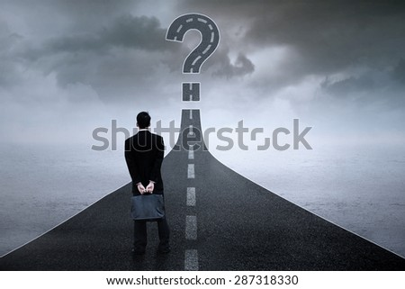 Back view of male entrepreneur standing on the highway while looking at the question sign - stock photo