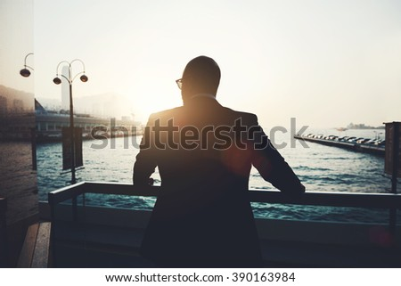 Back view of male successful entrepreneur enjoying evening sunset while standing outdoors in marina port.Silhouette of prosperous businessman is thinking about future signing a contract with investors - stock photo