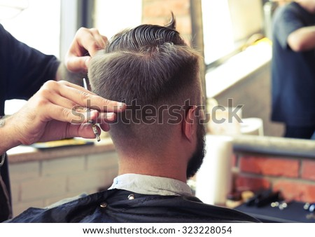 back view of man in barber shop. barber cutting hair with scissors - stock photo