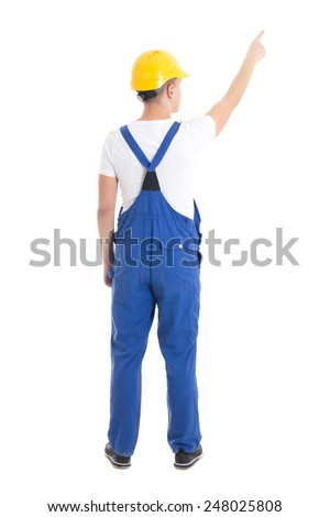 back view of man in blue builder uniform pointing at something isolated on white background