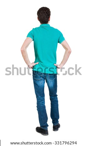 Back view of man in jeans. Standing young guy. Rear view people collection.  backside view of person.  Isolated over white background. A guy in a T-shirt is stylish aquamarine hands on hips. - stock photo