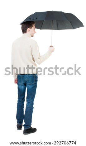 Back view of man in jeans under an umbrella. Standing young guy.   Isolated over white background. A guy in a white warm sweater hiding from the rain under an umbrella, and someone... - stock photo