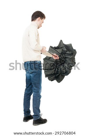 Back view of man in jeans  with umbrella. Standing young guy. Rear view people collection.  backside view of person.  Isolated over white background. A guy in a white warm sweater folded umbrella. - stock photo