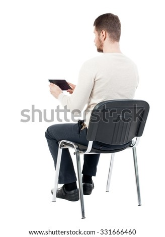 back view of man sitting on chair and looks at the screen of the tablet.  businessman watching. Rear view people collection.  backside view of person.  Isolated over white background. - stock photo