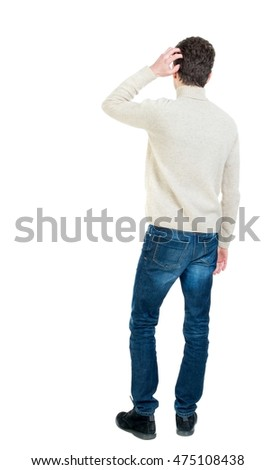 Back view of man . Standing young guy. Curly short-haired guy in a white jacket wool scratching hand to head.