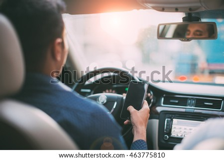 Back view of man using mobile phone at the car