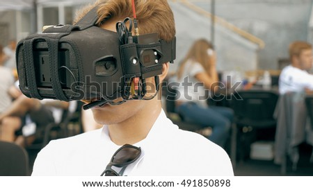 Back view of man watching flight of FPV drone using Virtual Reality glasses. Drone control training process in sunny day. Quadrocopter competitions outdoors.