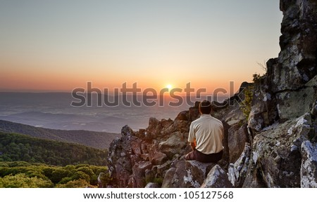 Back view of man watching sunset from rocky summit of Stony Man on Skyline Drive in Virginia - stock photo