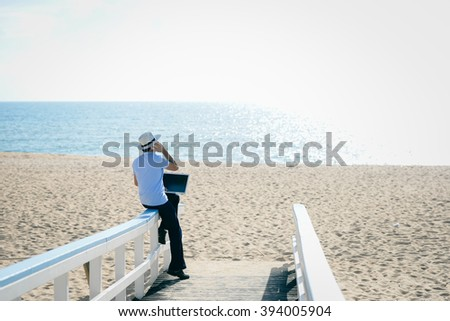 Back view of man with laptop on sunny beach of island, talking on smartphone. Vacation holiday - stock photo