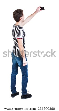 Back view of man with tablet. Standing young guy. Rear view people collection.  backside view of person.  Isolated over white background. The guy in the striped shirt photographed on a mobile phone. - stock photo