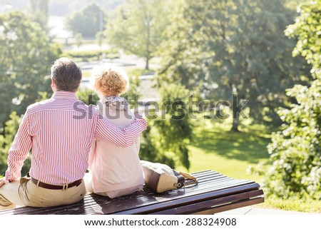 Back view of middle-aged couple relaxing on park bench - stock photo