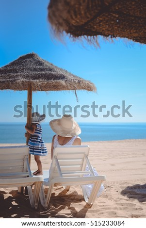 Back view of mother and baby sitting under an umbrella on beach sunny blue sky outdoors background