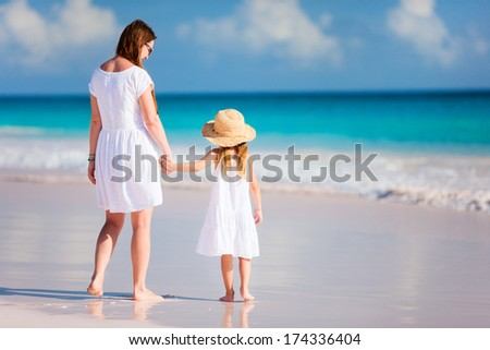 Back view of mother and daughter at Caribbean beach - stock photo