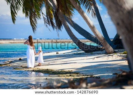 Back view of mother and daughter on a deserted island - stock photo