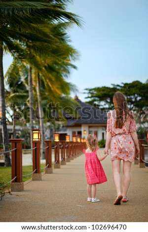 Back view of mother and daughter walking outdoors - stock photo