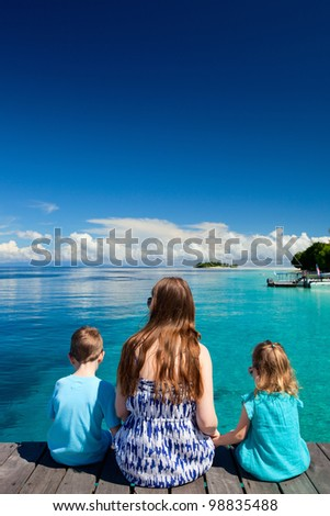 Back view of mother and kids sitting on wooden dock - stock photo