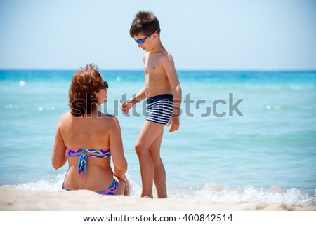 Back view of mother and son enjoying tropical beach vacation, Thailand, Asia - stock photo
