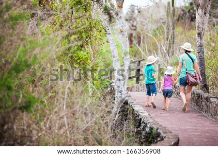 Back view of mother and two kids hiking in a park - stock photo