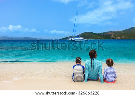 Back view of mother and two kids walking on a tropical beach enjoying summer vacation - stock photo