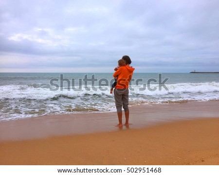 Back view of mother with child on beach dark cloud sky outdoors background. Book cover idea design style