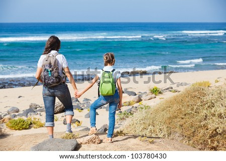 Back view of mother with her daughter walking on a beach, wearing jeans and white shirts - stock photo