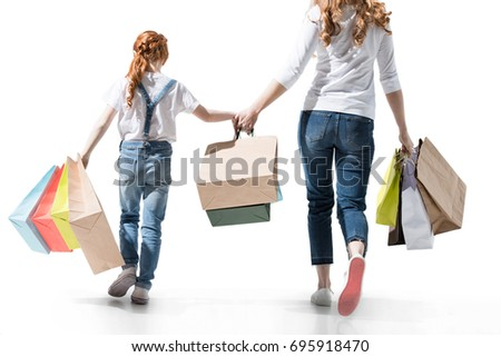 back view of mother with shopping bags walking together isolated on white
