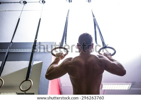 Back view of muscular man doing ring gymnastics in crossfit gym - stock photo