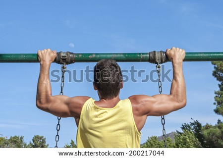 Back view of muscular man in yellow tank top performing pull up exercise on playground swing outdoors  - stock photo
