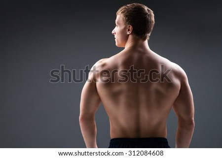 Back view of muscular young man  shows the different movements and body parts - stock photo