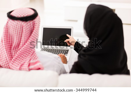 back view of muslim couple pointing at laptop screen - stock photo