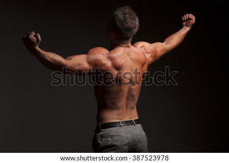 back view of naked muscular man in pants on gray - stock photo